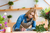 beautiful young female florist taking notes at workplace