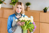 young female florist in apron holding beautiful tulips in vase and looking at camera