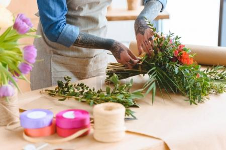 cropped shot of young florist with tattooed hands arranging flower bouquet at workplace