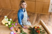 high angle view of beautiful young florist in apron standing at workplace and looking at camera