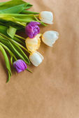 top view of beautiful colorful tulips on craft paper