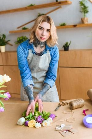 Photo pour Belle jeune fleuriste femme en tablier, regardant la caméra tout en travaillant dans le magasin de fleurs - image libre de droit