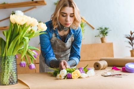 young florist working with beautiful tulip flowers at workplace