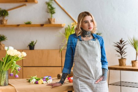 young florist leaning at table and looking away in flower shop