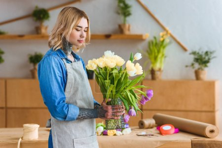 beautiful young florist in apron holding vase with tulip flowers