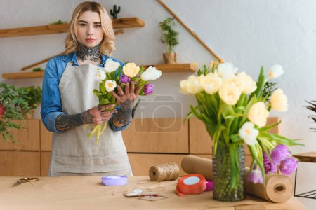 young florist in apron holding beautiful tulips and looking at camera in flower shop