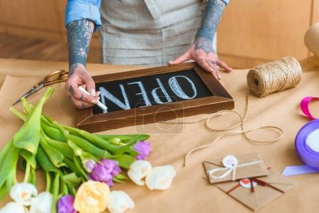 cropped shot of young tattooed florist writing word open on board at workplace