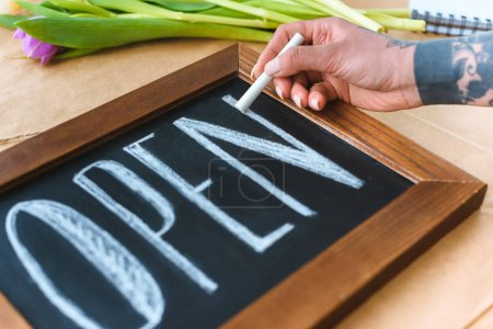 close-up partial view of young florist writing word open on board