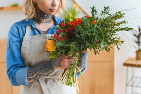cropped shot of young florist with tattoos holding flower bouquet
