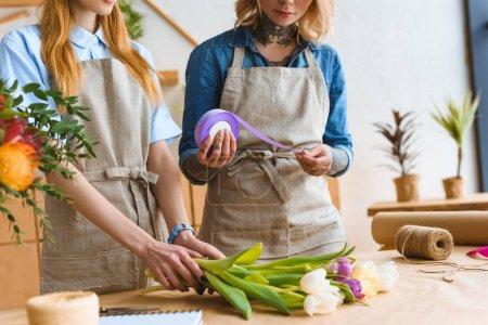 Photo pour Recadrée tir des jeunes fleuristes femelles organiser ensemble les bouquet de fleurs - image libre de droit