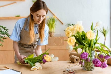 young florist in apron arranging beautiful tulip flowers at workplace