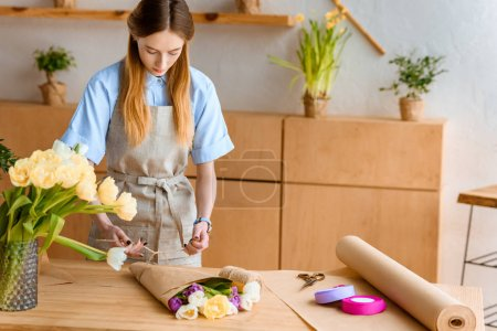 beautiful young florist in apron arranging flower bouquet at workplace