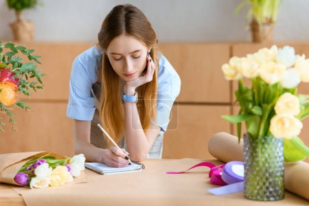 beautiful young florist taking notes in notebook at workplace