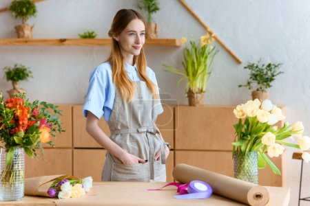 smiling young florist in apron looking away in flower shop