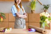 cropped shot of smiling young florist standing with crossed arms in flower shop