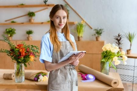 beautiful young florist holding digital tablet and smiling at camera in flower shop