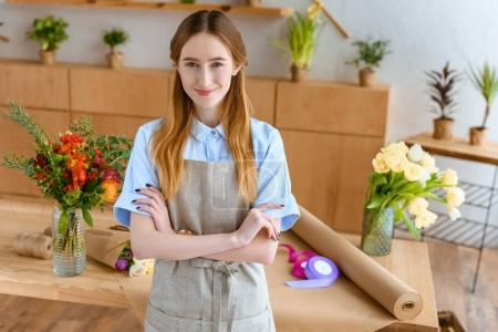beautiful young florist in apron standing with crossed arms and smiling at camera in flower shop