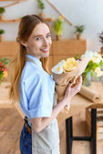 young female florist holding beautiful bouquet of tulips and smiling at camera in flower shop