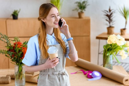 smiling young florist holding coffee to go and talking by smartphone