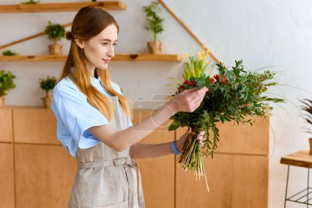 beautiful smiling young female florist in apron holding bouquet of flowers
