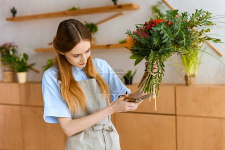 young female florist in apron cutting flowers