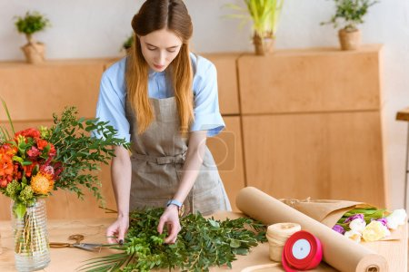 beautiful young florist in apron arranging green plants in flower shop