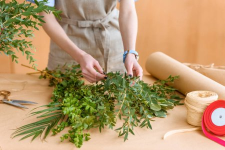 mid section of young florist in apron arranging green plants in flower shop