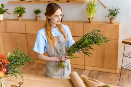 high angle view of smiling young florist in apron holding green plants in flower shop