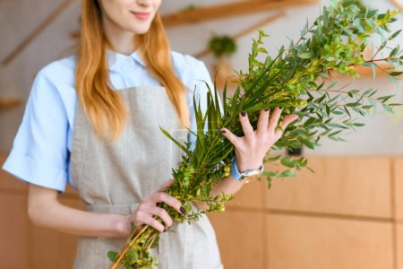 cropped shot of smiling young florist in apron holding green plants