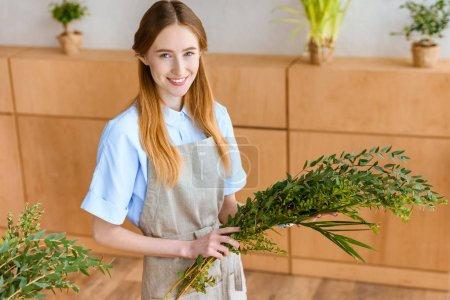 Photo for Beautiful young female florist holding green plants and smiling at camera in flower shop - Royalty Free Image
