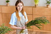 beautiful young female florist holding green plants and smiling at camera in flower shop