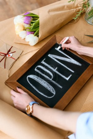 Photo for Cropped shot of young florist writing word open with chalk on board - Royalty Free Image