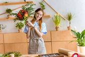 beautiful young florist in eyeglasses holding flower bouquet and smiling at camera at workplace