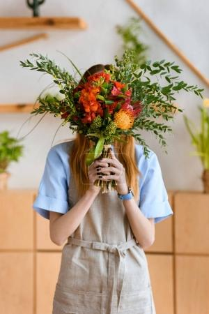 young florist in apron hiding face behind beautiful flower bouquet