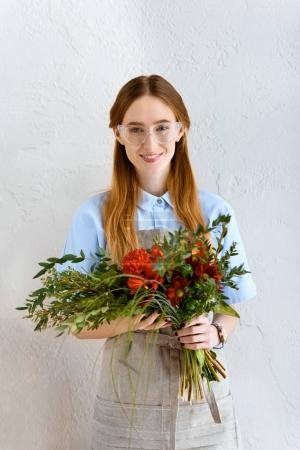 beautiful young florist in eyeglasses hoding flower bouquet and smiling at camera
