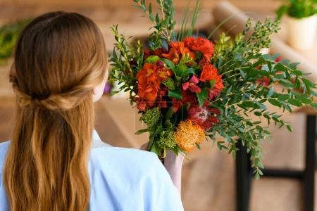 Photo pour Vue arrière du jeune fleuriste tenant beau bouquet de fleurs - image libre de droit