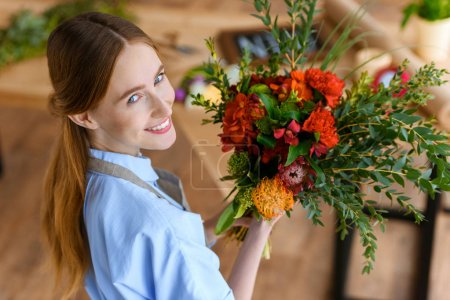 high angle view of beautiful young florist holding bouquet of flowers and smiling at camera