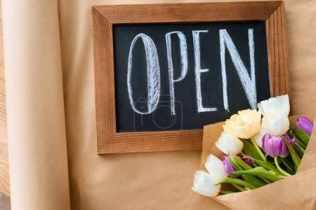 top view of beautiful tulips and open sign on craft paper