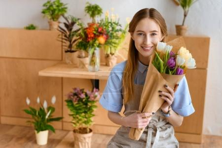 beautiful young florist holding bouquet of tulips and smiling at camera in flower shop