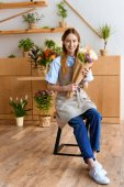 beautiful young florist holding bouquet of tulips and smiling at camera while sitting in flower shop