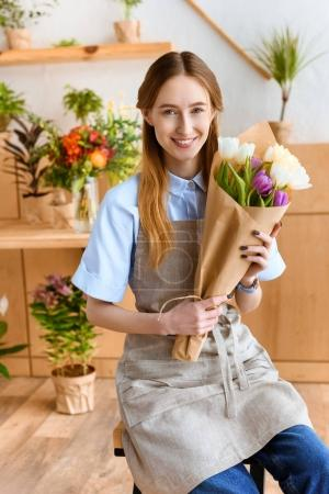 beautiful young florist holding bouquet of tulips and smiling at camera