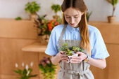 beautiful smiling young florist holding succulents in pots in flower shop