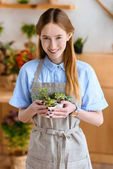 beautiful young woman in apron holding succulents in pots and smiling at camera in flower shop