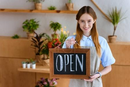 beautiful young florist in apron holding sign open and smiling at camera in flower shop