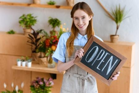 beautiful young woman in apron holding sign open and smiling at camera in flower shop