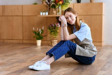 Photo pour Belle fleuriste jeune assis sur le plancher et souriant à la caméra à la boutique de fleurs - image libre de droit