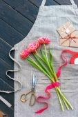 flores de tulipán hermosa con sobres, cinta y tijeras en delantal