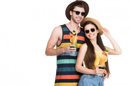 smiling couple in sunglasses and hats holding summer cocktails, isolated on white