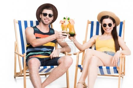 couple relaxing on beach chairs and clinking glasses with cocktails, isolated on white