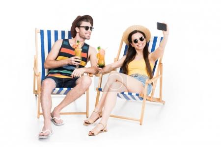 couple relaxing on beach chairs with cocktails and taking selfie, isolated on white